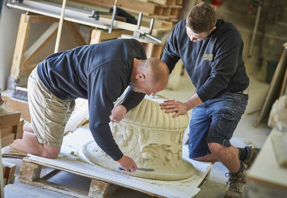 Chilstone staff removing cast stone urn from mould and finishing the stone edges in the workshop