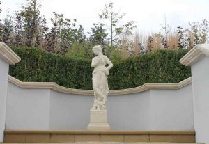 Concrete coping stone behind a beautiful cast stone statue