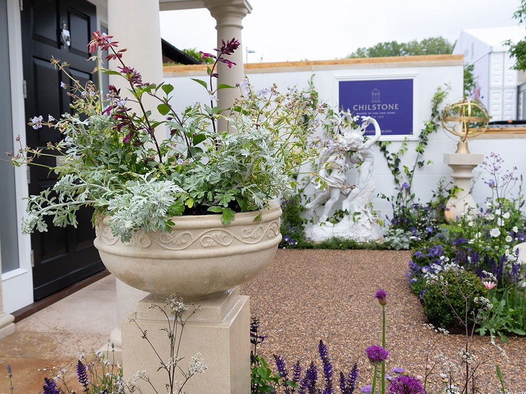 Cast stone replica of Hurlingham Club bowl planted with greenery set in cast stone trade stand at Chelsea flower show