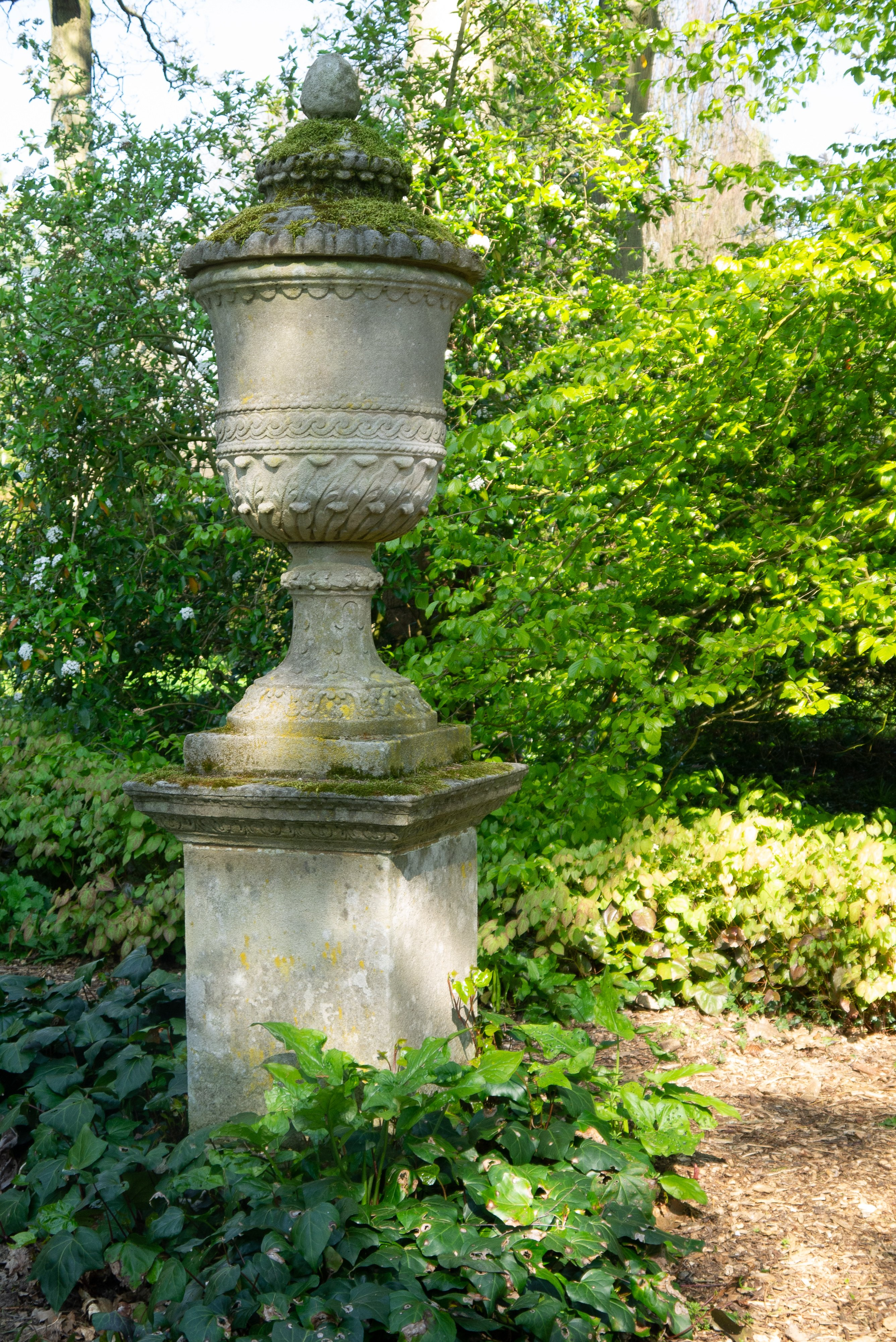 Cast stone garden urn with leafy green background