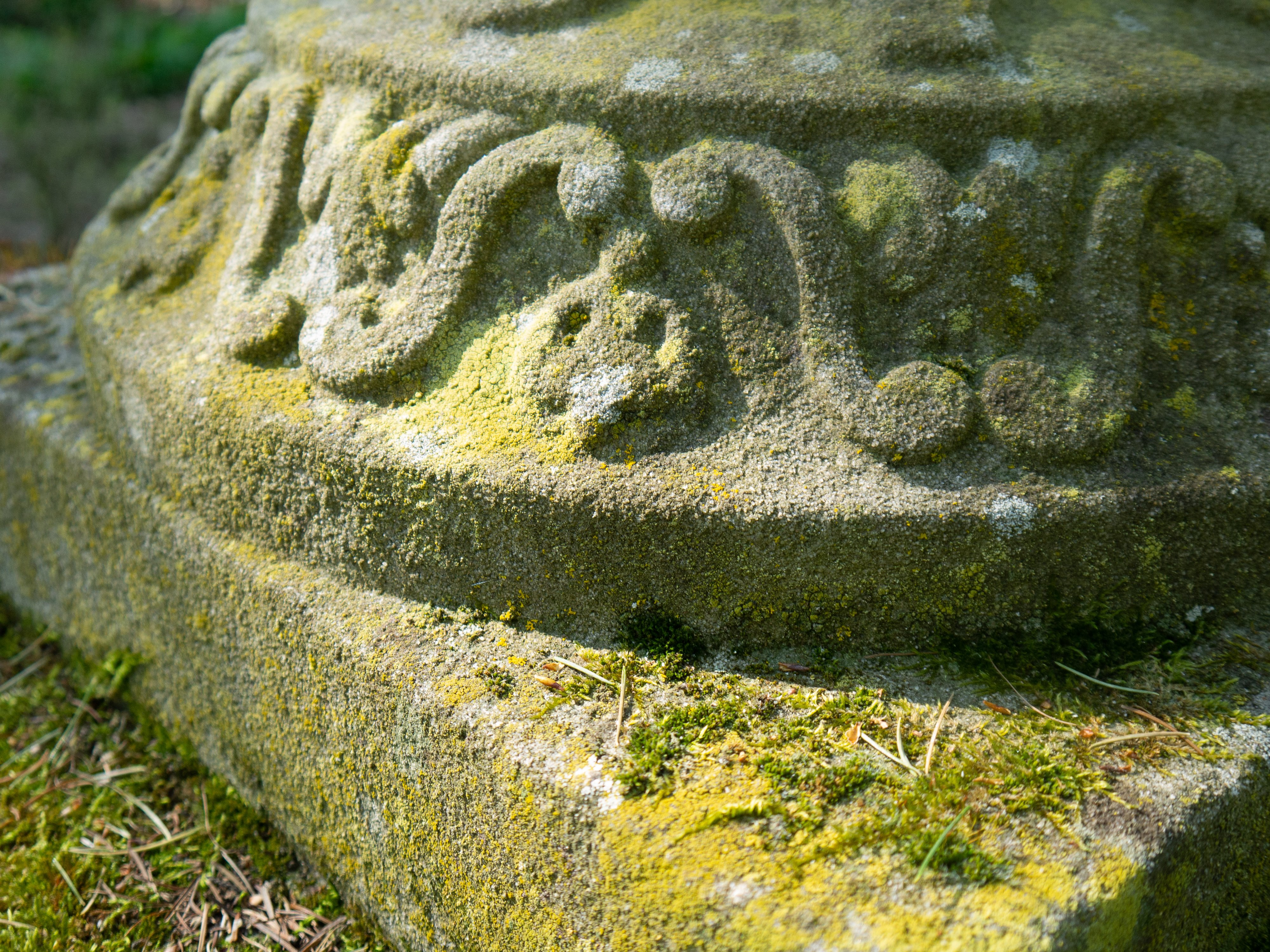 Close up of weathered old cast stone garden ornament with moss and lichen