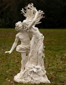 Statue of Greek Gods and Goddesses Apollo and Daphne in a grassy garden