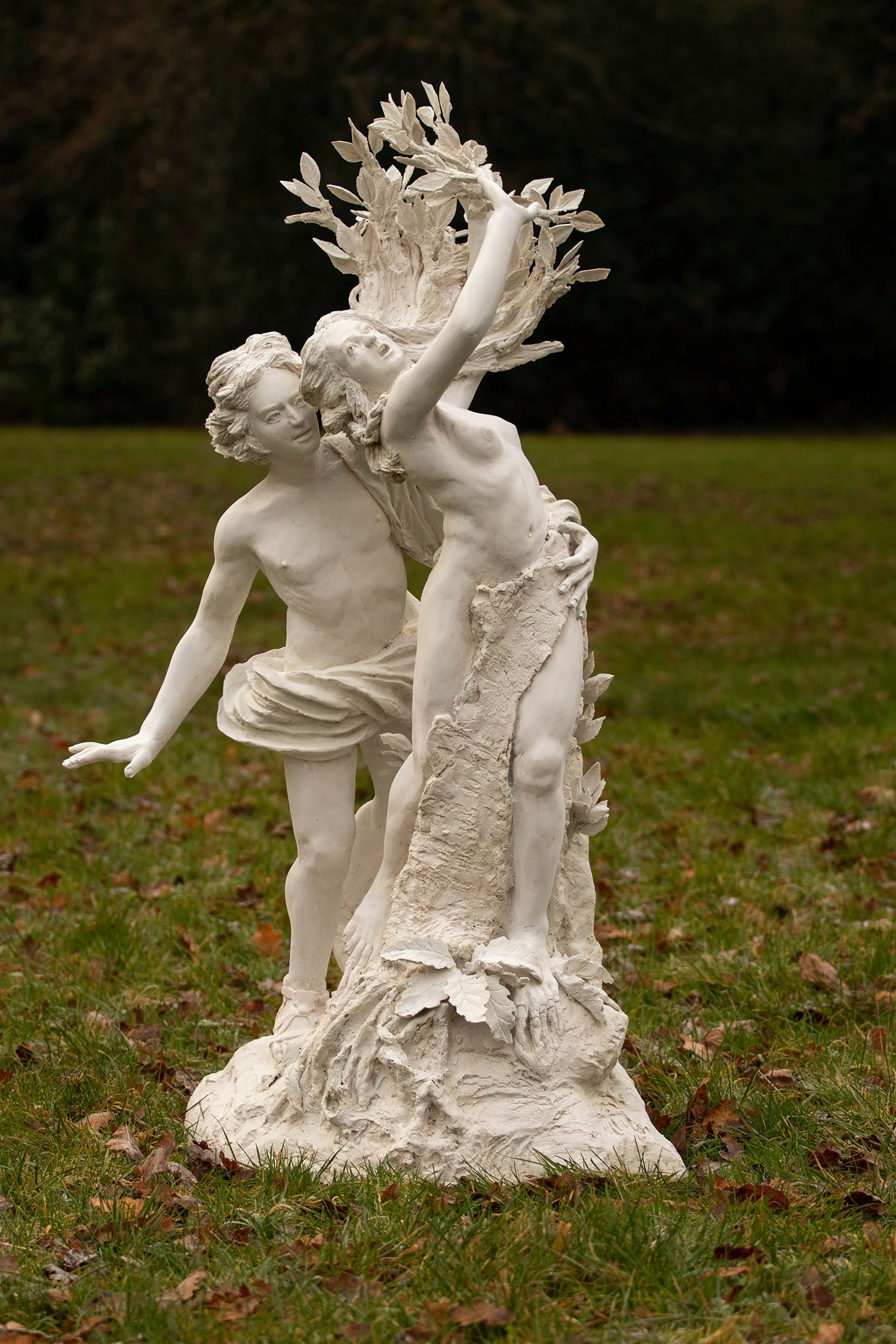 Cast stone replica Greek sculpture of Apollo and daphne on a grassy background