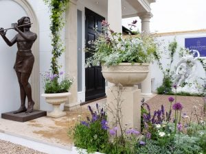 Cast stone planter and portico with wildflowers on Chelsea flower show trade stand