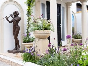 Chelsea show garden featuring cast stone garden ornaments, portico and bronze resin sculpture of woman playing the flute