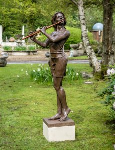 Replica bronze sculpture of a woman playing a flute standing on a concrete base with daffodils in background