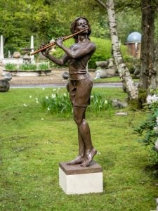 bronze resin sculpture of a woman playing the flute on a pedestal with daffodils in the background