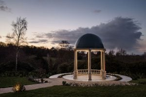 Stone garden pavilion glowing at dusk in the grounds of the spa hotel