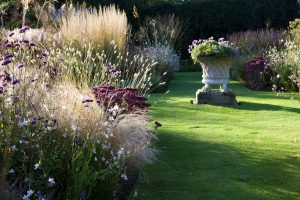 Stone garden planter in a sunny spot next to borders planted with different grasses