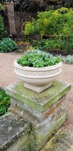 New cast stone planter planted with flowers on top of an old wall