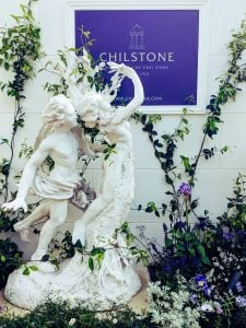 Copy of Apollo and Daphne Greek God and Goddess statue in marble resin in front of white wall with vines, purple flowers and purple Chilstone sign