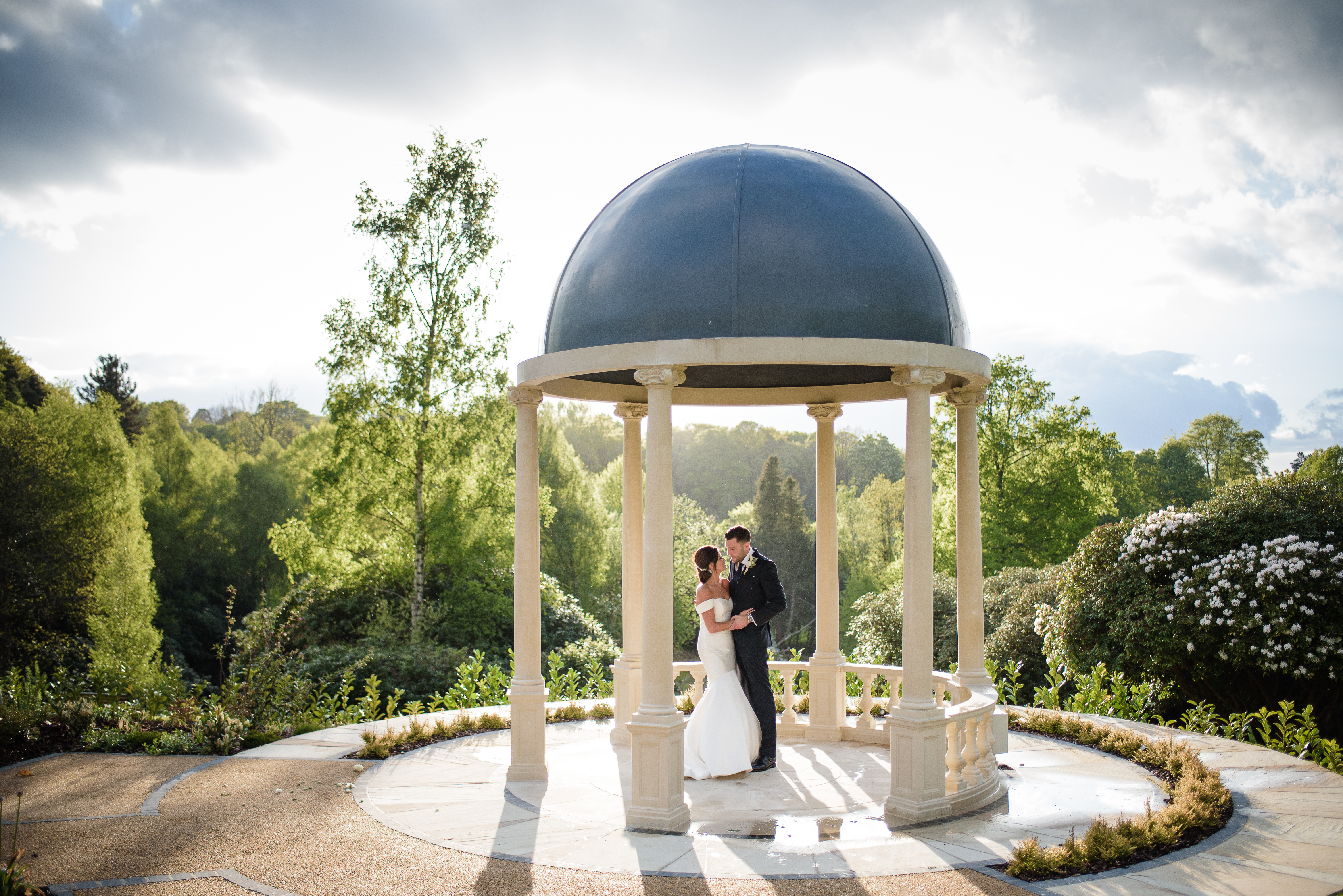 Sun shines on a bride and groom through a garden pavilion used as an outdoor wedding pagoda in the grounds of the spa hotel