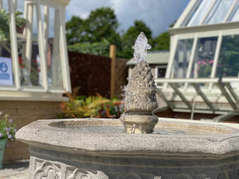 Stone fountain spurting water at Hampton Court flower show