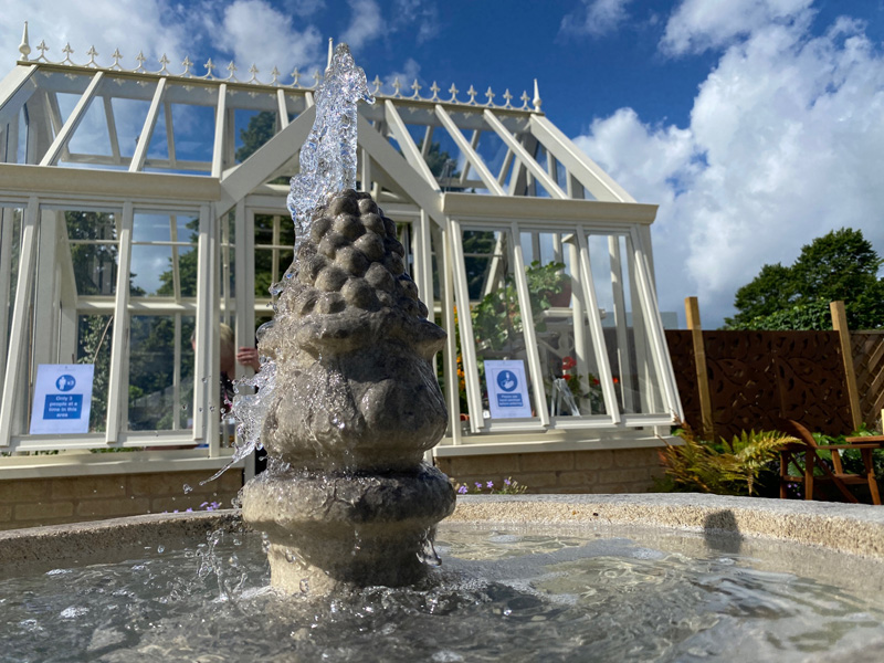 Stone garden fountain in front of glasshouse